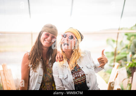 couple of crazy females friends have fun and enjoy lifestyle wearing hippy old retro style clothes and accessories. fashion and friendship for young caucasian women - Stock Photo