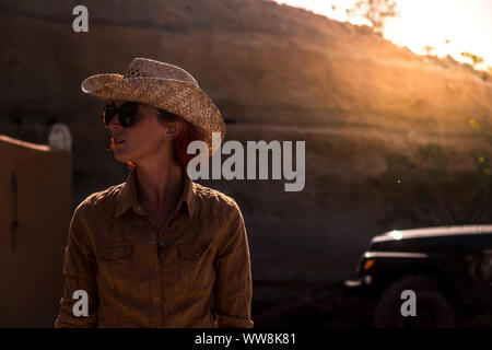 beautiful young woman in country side with golden backlight from sunset on the background. living different for happy lifestyle concept. - Stock Photo