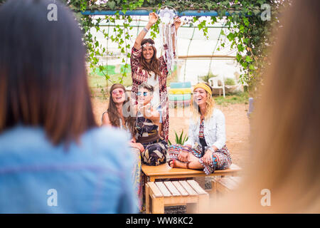 nice group of caucasian colored clothes young woman stay together in friendship. focus on the brown long hair smiling one. group of happy people in leisure activity outdoor - Stock Photo
