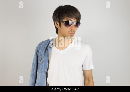Young Asian Man in Jeans Jacket or Denim Jacket Wear Sunglasses and Show T-Shirt. Denim or Jeans Jacket Men Fashion on Gray Background - Stock Photo