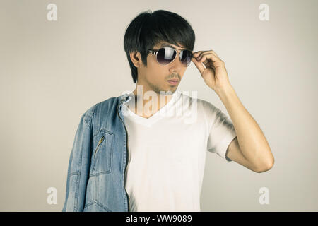 Young Asian Man in Jeans Jacket or Denim Jacket Touching Sunglasses and Show White T-Shirt. Denim or Jeans Jacket Men Fashion on Gray Background - Stock Photo