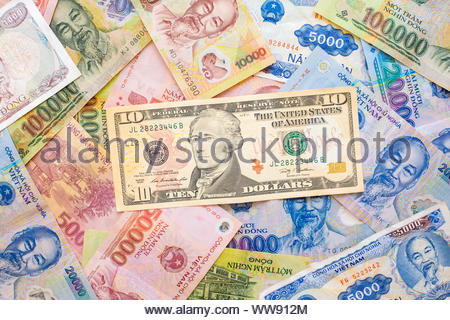 United States dollars (10 USD) on top of various denominations of Vietnamese Dong currency, paper banknotes, money - Stock Photo