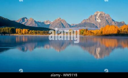 A beautiful early morning landscape scene at Oxbow Bend in the Snake River, with Mount Moran and autumn tree color reflected in the smooth water. Gran - Stock Photo