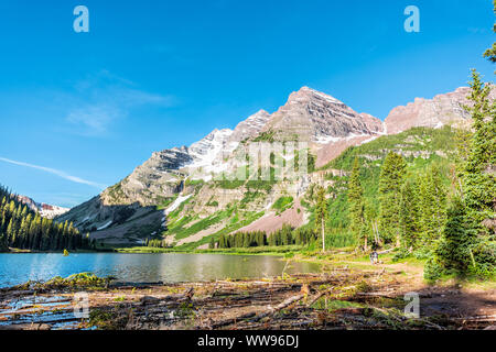 Aspen, USA - July 19, 2019: Maroon Bells rocky mountain peak view with Creater Lake in Colorado in summer on trail wide angle view with people