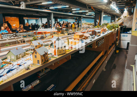 Behind the scenes at Miniatur Wunderland, an enormous display of miniature scenes complete with tiny electric vehicles, model train sets, and scenery - Stock Photo