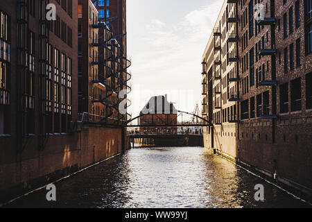 Looking down the canals with old warehouses on either side in the late afternoon in Hamburg, Germany - Stock Photo