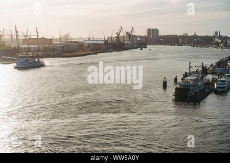 Looking out over the Norderelbe (Northern Elbe), Port of Hamburg, Germany as boats drift by in the late afternoon sun - Stock Photo