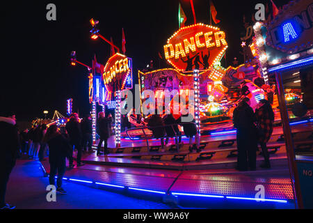 Teenagers watch the cars on a spinning fairground ride zip past them at a night time fairground in Hamburg, Germany - Stock Photo