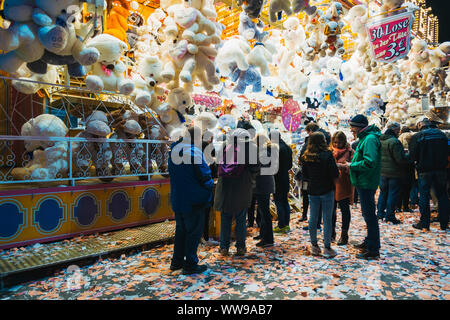 Dozens of stuffed toy animals hang above a raffle-like game while fair attendees walk past, one night at a fairground in Hamburg, Germany - Stock Photo