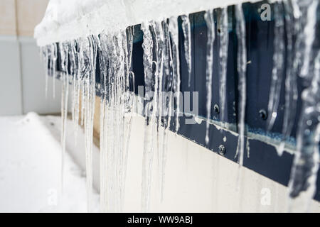 Icicles on building in winter in Sierra Nevada - Stock Photo
