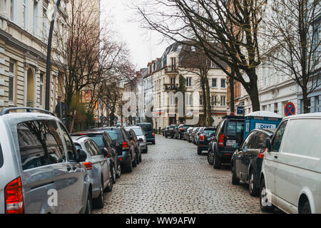 Leafless trees line the suburban streets of Altona, Hamburg, on a quiet grey winters morning - Stock Photo