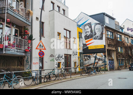 Street art and chained bicycles line the suburban streets of Altona, Hamburg, on a quiet grey winters morning - Stock Photo