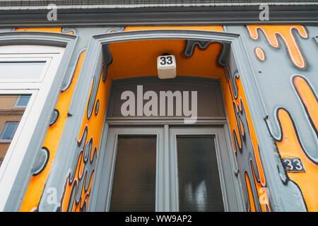 A bright orange and grey lava-like painted doorway of Altona, Hamburg, on a quiet grey winters morning - Stock Photo