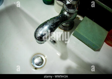 old sink water tap in dark - Stock Photo