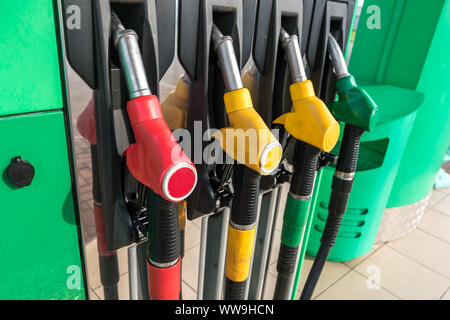 Gas and petrol station. Guns for refueling at a gas station. Detail of a petrol pump different colors in gas station. Close up on fuel nozzle in oil d - Stock Photo