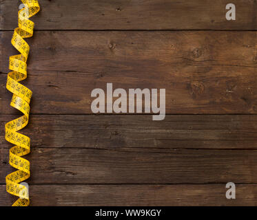 A coiled yellow measuring tape on a wooden table - Stock Photo