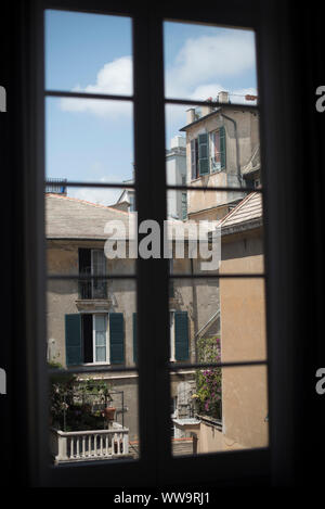 Genoa, Italy - July 3, 2018: A summertime view through a window of buildings with green shutters in the historic central district of Genoa, Italy. - Stock Photo