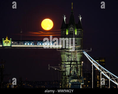 London, UK. 13th Sep, 2019. A full moon rises behind Tower Bridge. The Full Moon in September is called the Harvest Moon. Credit: Siu K Lo/Alamy Live News - Stock Photo