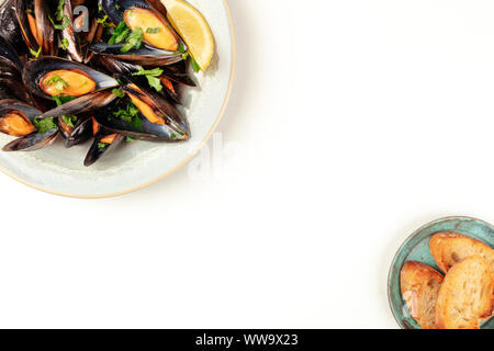 Marinara mussels, moules mariniere, shot from the top on a white background with toasted bread and copy space, Belgian food design template - Stock Photo
