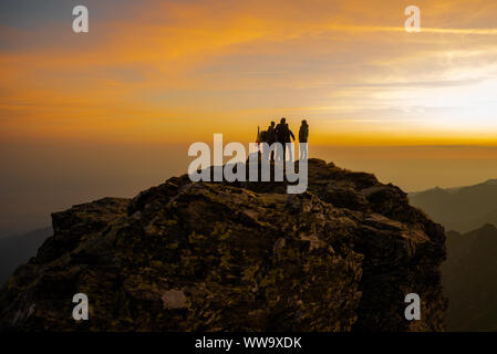 Group of tourists waiting for sunrise on the top of Fagaras mountains, Romania, looking towards Moldoveanu Peak - Stock Photo