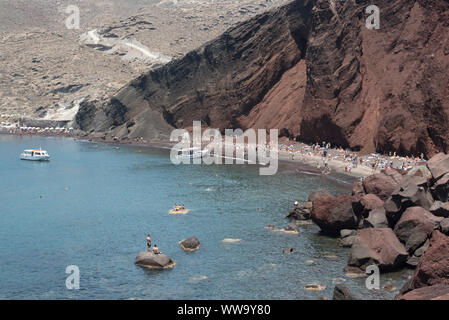 Santorini, Greece - June 24, 2018: Crowds and boats on Red Beach, a popular destination on the southern coast of Santorini. - Stock Photo
