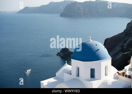 Santorini, Greece - June 24, 2018: Blue seas surround the famous blue domes of Oia, a popular tourist town on the northern end of Santorini. - Stock Photo