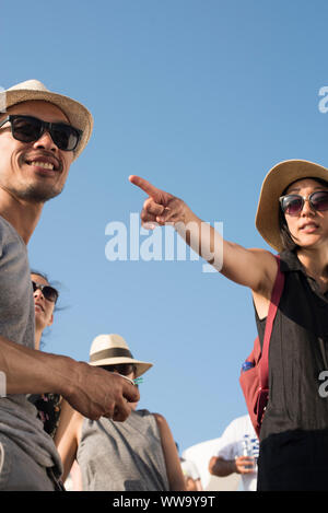 Santorini, Greece - June 24, 2018: Tourists in straw hats and sunglasses are framed against the blue midday skies of Oia, a popular tourist destinatio - Stock Photo
