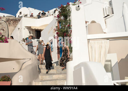 Santorini, Greece - June 24, 2018: Tourists in straw hats and sunglasses wander down stone stairs in Oia, a popular tourist destination on the norther - Stock Photo