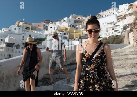 Santorini, Greece - June 24, 2018: Tourists in straw hats and sunglasses wander down stone steps toward Ammoudi Bay in Oia, a popular tourist destinat - Stock Photo