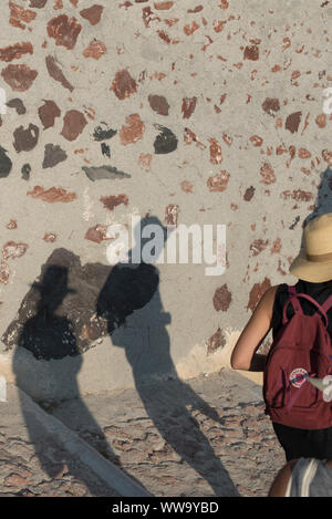 Santorini, Greece - June 24, 2018: The shadows of tourists in straw hats wandering down stone steps toward Ammoudi Bay in Oia, a popular tourist desti - Stock Photo
