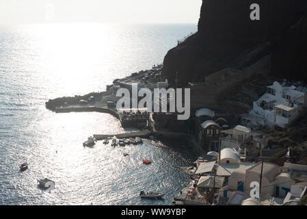 Santorini, Greece - June 24, 2018: Late afternoon sunshine lights up Ammoudi Bay in Oia, a popular tourist destination in Santorini. - Stock Photo