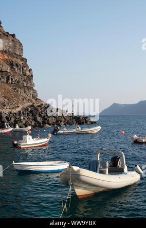 Santorini, Greece - June 24, 2018: Fishing boats moored under rocky cliffs in Ammoudi Bay in Oia, Santorini. - Stock Photo