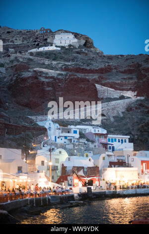 Santorini, Greece - June 24, 2018: Dinner crowds pack the lighted restaurants on the shore of Ammoudi Bay in Oia, a popular tourist destination on the - Stock Photo