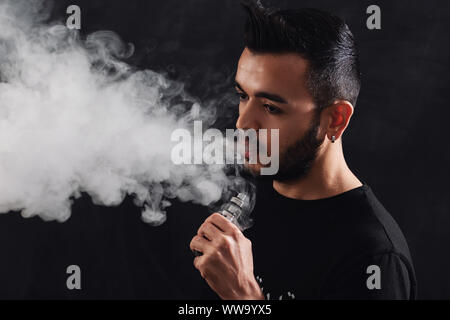 Young man with beard vaping electronic cigarette on black background. - Stock Photo