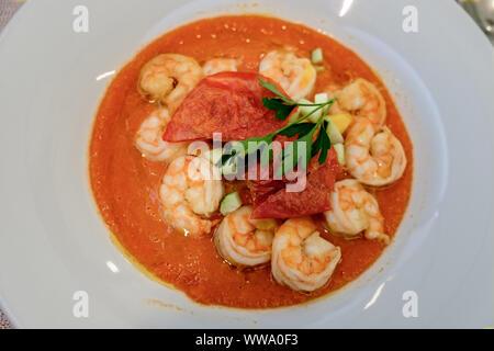 A fantastically tasty shrimps gazpacho on a large white plate, Vittorio Veneto, Italy. - Stock Photo