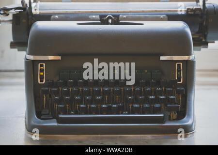 Old retro typewriter standing on the windowsill. - Stock Photo