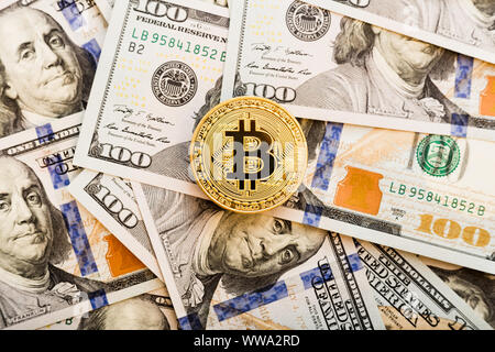 Golden Bitcoin coin on a us dollars close up. - Stock Photo