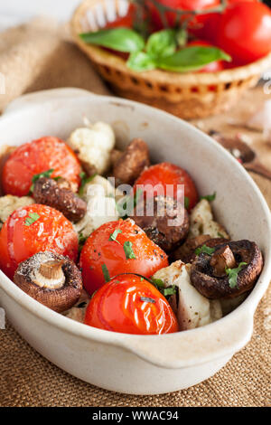 Assorted vegetables baked in oven in ceramic bowl. Grilled tomatoes, mushrooms, cauliflower - Stock Photo