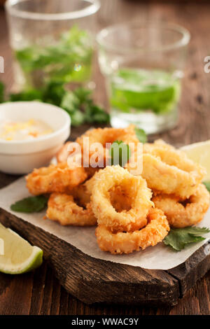 Fried calamari rings on wooden cutting board with lemon and parsley - Stock Photo