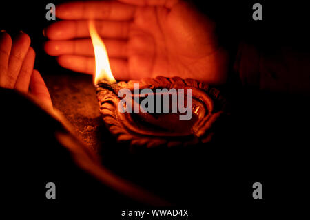 Hand holding or protecting diya or oil lamp, lantern during Diwali celebration. Background picture for Indian Hindu festival Diwali. - Stock Photo