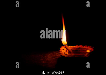 Traditional clay diya or oil lamp lit during Diwali celebration as well as kali puja isolated on black background with space for text.