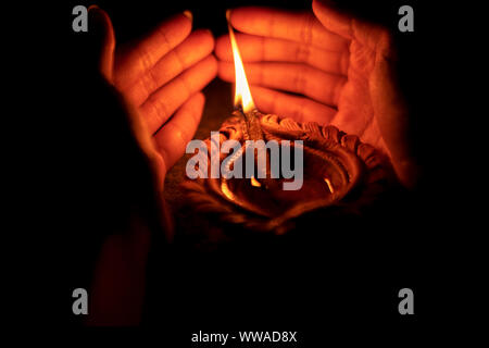 Indian girl or woman holding or protecting traditional clay diya or oil lamp on Diwali celebration with copy space isolated on black background. - Stock Photo