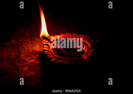 Close up image of a lit clay diya or lamp on floor on Diwali - an Indian hindu festival of lights isolated on black background. - Stock Photo