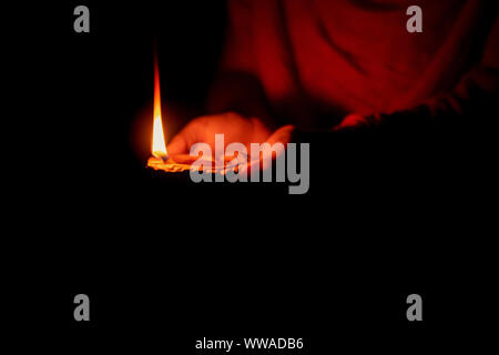 Diwali or deepavali photo with female holding oil lamp or diya during festival of light with space for text isolated on black background. - Stock Photo