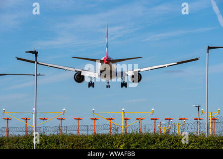British Airways jet airliner plane landing at London Heathrow Airport in Hounslow, London, UK behind runway approach threshold lights. Space for copy - Stock Photo