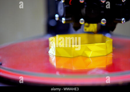3d printer while printing a yellow object close-up close-up. Progressive modern additive technologies 4.0 industrial revolution - Stock Photo