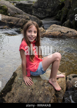 Holiday snap of 9 year old girl sitting on a rock in Scotland - Stock Photo