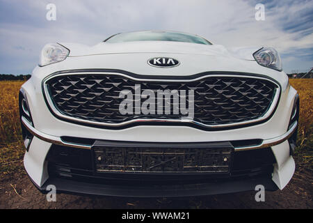 Ufa, Russia, 1 July, 2019: car Kia Sportage 2.0 CRDI awd or 4x4, white color, parked on the road, next to a large rock, with a beautiful blue sky in t - Stock Photo