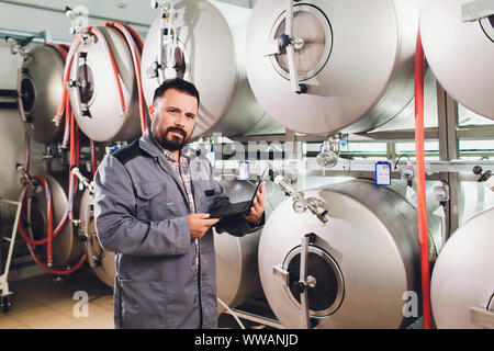 Portrait of brewer who is making beer on his workplace in the brew-house. - Stock Photo