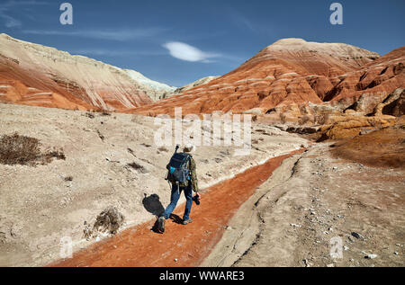 Tourist with backpack and camera walking at the dusty canyon on surreal red mountains against blue sky in the desert - Stock Photo